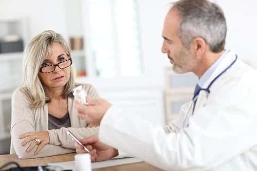 доктор показывает женщине банку с таблетками