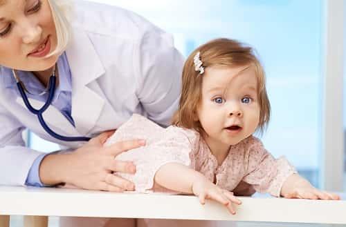 доктор держит девочку