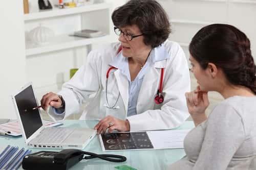 врач что-то показывает на мониторе пациенту