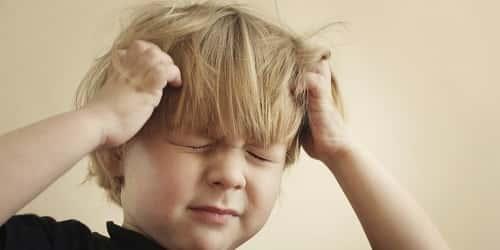 ребенок держится за голову