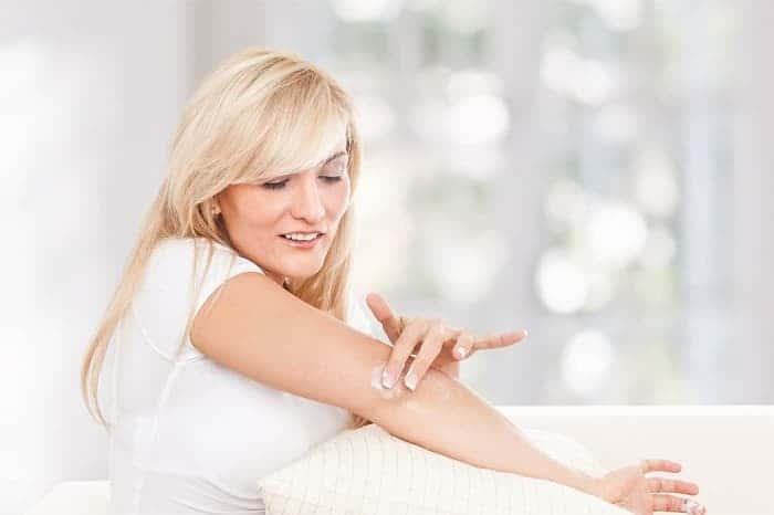 Женщина мажет руку