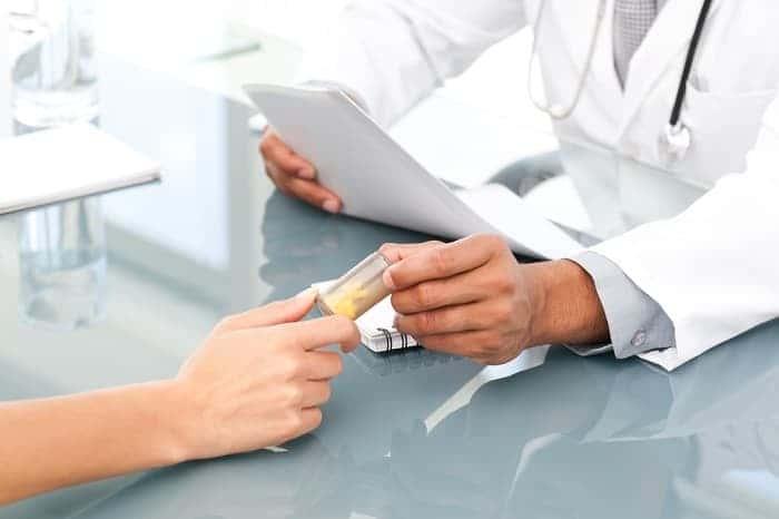Доктор дает таблетки пациенту