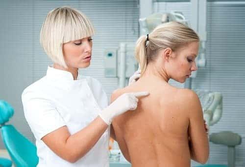 Доктор указывает на спину пациентке